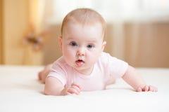 Lustiges Baby, das auf Bett liegt Stockbilder