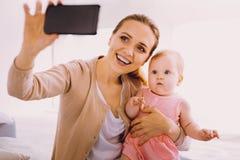 Lustiges Baby, das beim Sehen eines modernen Gerätes überrascht schaut Lizenzfreies Stockfoto