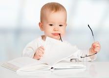 Lustiges Baby, das ein Buch liest stockfotos