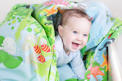 Lustiges Baby, das im Bett unter blauer Decke spielt Lizenzfreie Stockfotos