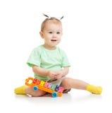 Lustiges Baby, das mit dem Xylophon lokalisiert spielt Lizenzfreie Stockfotos