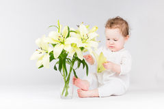 Lustiges Baby, das mit Lilienblumen spielt Stockbild