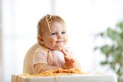 Lustiges Baby, das Nudel isst Schmutziges Kind isst Spaghettis mit auf Tabelle zu Hause handssitting stockbild