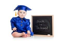 Lustiges Baby in der Akademikerkleidung an der Tafel Stockfoto