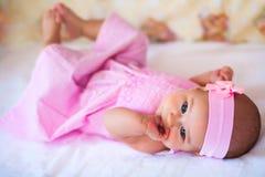 Lustiges Baby in einem rosa Kleid Stockbild