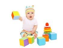 Lustiges Baby im gestreiften Hut, der mit Spielwaren spielt Stockfotografie