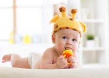 Lustiges Baby im Giraffenhut, der auf seinem Bauch in der Kindertagesstätte liegt Kleinkind, das Nibblerspielzeug verwendet Stockfotografie