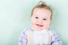 Lustiges Baby im purpurroten Kleid, das auf Grün liegt, strickte Decke Stockbild