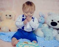 Lustiges Baby isst einen geschmackvollen Kuchen Lizenzfreie Stockfotos