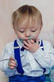 Lustiges Baby isst einen geschmackvollen Kuchen Lizenzfreie Stockbilder