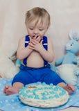 Lustiges Baby isst einen geschmackvollen Kuchen Stockbilder