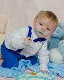 Lustiges Baby isst einen geschmackvollen Kuchen Lizenzfreies Stockfoto