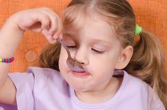 Lustiges Baby isst mit einem Löffel Stockbilder