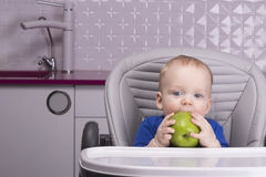 Lustiges Baby mit großem grünem Apfel in der Küche Stockbilder