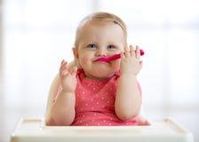 Lustiges Baby mit Löffel in ihrem Mund Schönes Kindermädchen, das im Hochstuhl und in Wartelebensmittel sitzt Nahrung für Kinder stockfoto
