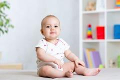 Lustiges Babykindermädchen, das auf Boden im Kinderraum sitzt stockfotografie