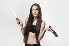 Lustiges Bild der jungen Frau Zucchini und Messer halten Lizenzfreie Stockfotografie