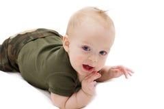 Lustiges blauäugiges Baby, das auf die weiße Decke gegen den lokalisierten weißen Hintergrund betrachtet Kamera kriecht lizenzfreie stockbilder