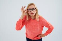 Lustiges blondes in den Gläsern, die entlang der Kamera anstarren Stockfotografie