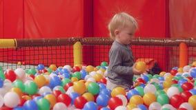 Lustiges blondes Kleinkind mit dem elektrifizierten Haar im trockenen Pool mit Bällen stock video