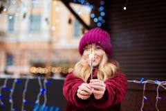 Lustiges blondes Mädchen, das glühende Bengal-Lichter am Weihnachten hält Lizenzfreie Stockbilder