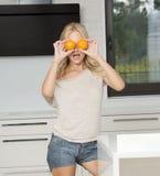 Lustiges blondes Mädchen, das orange Gläser tut Lizenzfreie Stockfotos
