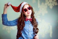 Lustiges Brunettemädchen im Weihnachtshut und -herzen Stockfoto