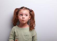Lustiges denkendes Kindermädchen, das Lutscher isst und oben schaut Lizenzfreie Stockbilder