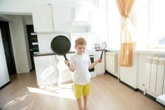Lustiges europ?isches Cheftanzen des kleinen Jungen, gl?ckliches Wochenende, Junge m?chte Pfannkuchen machen, aber die Bratpfanne lizenzfreies stockfoto