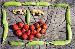 Lustiges Fruchtgesicht im Erbsenrahmen auf hölzernem Hintergrund Stockbild