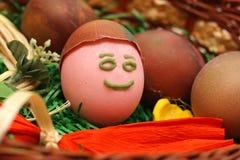 Lustiges gemaltes lächelndes Osterei im Korb Rechte Ansicht Stockfotos