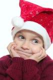 Lustiges Gesicht des Kindes roten Santa?s Hubcap tragend. Lizenzfreie Stockbilder