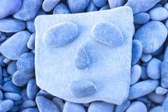 Lustiges Gesicht gemacht auf einem Strand mit Steinen und Kieseln Stockbild