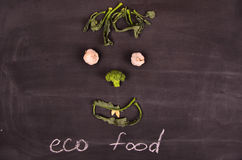 Lustiges Gesicht vom Gemüse auf schwarzem Boden Stockfotografie
