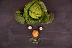 Lustiges Gesicht vom Gemüse auf schwarzem Boden Stockbilder