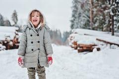 Lustiges glückliches Kindermädchenporträt auf dem Weg im schneebedeckten Wald des Winters mit Baumholzschlag auf Hintergrund Stockfotografie