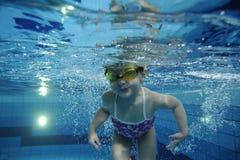 Lustiges glückliches Kleinkindmädchen, das unter Wasser in einem Pool mit vielen Luftblasen schwimmt Stockfotografie