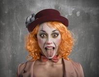 Lustiges Grimassenclown-Mädchenmädchen mit der Zunge draußen lizenzfreie stockbilder