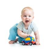 Lustiges Jungenbaby, das mit Spielzeugauto spielt Stockbild
