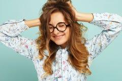 Lustiges junges hübsches Frauenhändchenhalten auf ihrem Kopf über blauem BAC Stockfoto