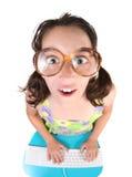 Lustiges junges Kind, das an einem Computer arbeitet Lizenzfreies Stockbild
