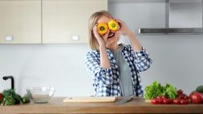 Lustiges junges Mädchen, das bedeckte Augen durch die gelben Pfeffer lächeln aufwirft, das Kochen genießend an der Küche stock footage
