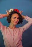 Lustiges junges Mädchen, das Schaumgummiringe über ihrem Kopf hält stockfoto