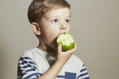 Lustiges Kind, das Apfel isst Little Boy Biokost Corn Flakes Früchte Stockbilder