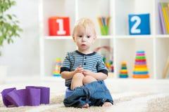 Lustiges Kind, das auf Kammertopf mit Toilettenpapierrollen sitzt stockbilder