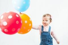 Lustiges Kind, das einen Ballon im Freien am Mohnblumenfeld hält Lizenzfreies Stockfoto
