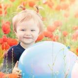 Lustiges Kind, das einen Ballon im Freien am Mohnblumenfeld hält Lizenzfreies Stockbild