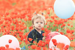 Lustiges Kind, das einen Ballon im Freien am Mohnblumenfeld hält Lizenzfreie Stockbilder
