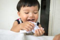 Lustiges Kind, das etwas unterschiedlich und das Lachen schafft Hand, die lego Wand aufbaut Stockfotos