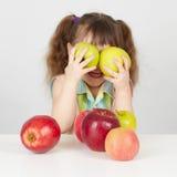 Lustiges Kind, das mit zwei Äpfeln spielt Stockfotografie